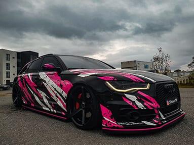 En svart bil med rosa og hvite striper