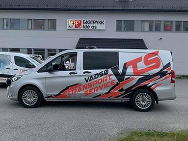 En grå varebil med tekst 'Vadsø Transport Service VTC'