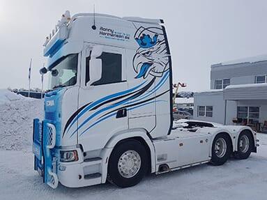 En hvit lastebil med noen blå og svarte striper og en tegning av et ørne hode med en blå krone på