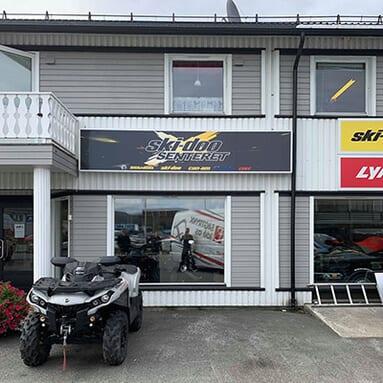En sølv farget ATV som står utenfor et grått bygg med et skilt der det står 'ski-doo Senteret'
