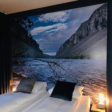 Et soverom med et bilde av en innsjø bak to senger