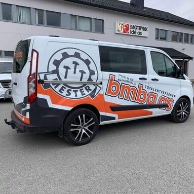 En hvit varebil med oransje strek, en logo med en grå sirkel med tre hammere i midten av den og teksten 'Mester' under, og oransje tekst 'bmba as'