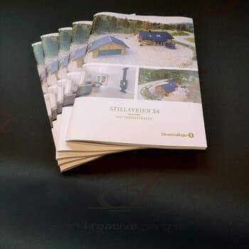 En bunke med fem kataloger som har bilder og tekst 'Stillaveien 58' på forsiden